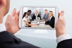 Biznesmen wideo konferencja na cyfrowej pastylce przy biurkiem Zdjęcia Stock