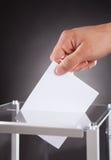 Biznesmen wkłada tajne głosowanie w pudełku na biurku Zdjęcie Royalty Free