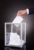 Biznesmen wkłada tajne głosowanie w pudełku na biurku obraz stock