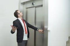 Biznesmen wprawiać w zakłopotanie ponieważ winda no pracuje Obrazy Royalty Free