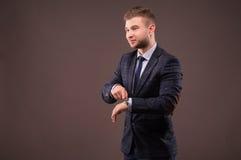 Biznesmen wskazuje oglądać i uśmiechy Fotografia Stock