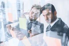 Biznesmen wskazuje przy kleistą notatką podczas gdy dyskutujący pracę z kolegą Zdjęcia Stock