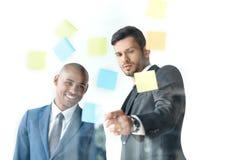 Biznesmen wskazuje przy kleistymi notatkami podczas gdy dyskutujący pracę z kolegą Fotografia Stock