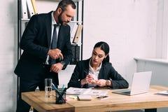 biznesmen wskazuje przy zegarkiem blisko koncentrował bizneswomanu przy miejsce pracy z laptopem zdjęcia royalty free