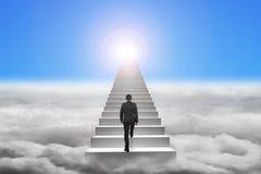 Biznesmen wspina się betonowych schodki z niebieskiego nieba światłem słonecznym Zdjęcia Stock