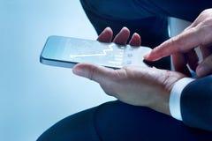 Biznesmen wzrasta na ekranie siedzi dotyka ekranu telefonu komórkowego statystyki i wykres Obrazy Stock