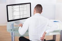 Biznesmen z backache używać komputer przy biurkiem obraz royalty free