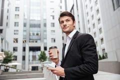 Biznesmen z bierze oddaloną kawową pozycję i używać telefon komórkowy Zdjęcie Royalty Free