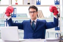 Biznesmen z bokserskimi rękawiczkami gniewnymi w biurze Fotografia Stock