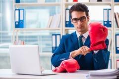 Biznesmen z bokserskimi rękawiczkami gniewnymi w biurze Zdjęcia Royalty Free