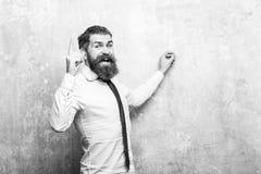 Biznesmen z brodą na szczęśliwej twarzy pisze z kredą zdjęcie royalty free