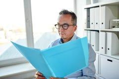 Biznesmen z falcówką i papiery przy biurem zdjęcia royalty free
