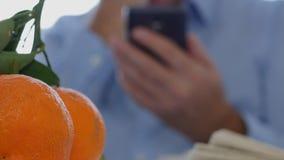 Biznesmen Z gazetą i owoc na Stołowym tekscie Używać telefon komórkowego zbiory