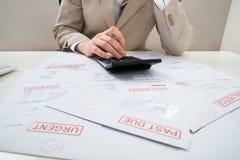 Biznesmen z kalkulatorem i niepłatnymi rachunkami obrazy stock