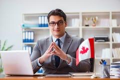 Biznesmen z kanadyjczyk flaga w biurze obrazy royalty free