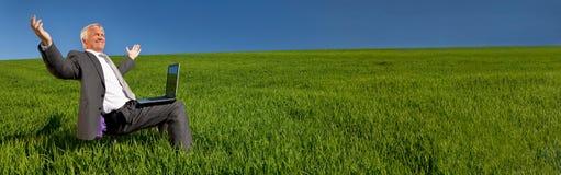 Biznesmen Z laptopem w zieleni pola sztandaru panoramie obraz stock