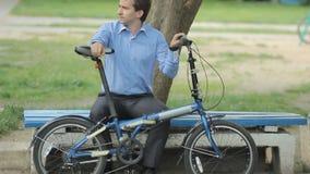 Biznesmen z małą rowerową jazdą ławka zdjęcie wideo
