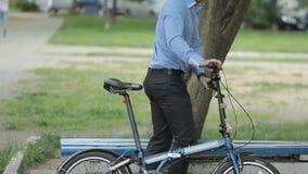 Biznesmen z małą rowerową jazdą ławka zbiory