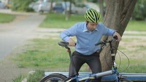 Biznesmen z małą rowerową jazdą od ławki zbiory wideo