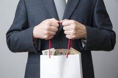 Biznesmen z pakunkiem pełno pieniądze w rękach zdjęcia royalty free