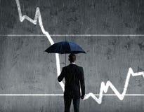 Biznesmen z parasolową pozycją nad szpaltowego diagrama backgroun Zdjęcia Stock