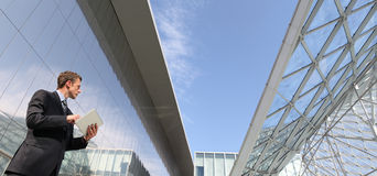 Biznesmen z pastylką która patrzeje daleko w niebo w scenie miastowy budynek, Zdjęcie Royalty Free