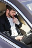 Biznesmen z pastylka komputerem w samochodzie obrazy stock