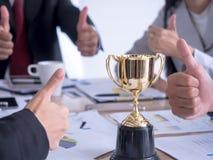 Biznesmen z pracą zespołową w pokazuje trofeum i kciuku w górę nagradzający dla biura w bramkowym i pomyślnym obrazy royalty free