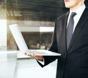 Biznesmen z rozpieczętowanym laptopem w jeden ręce obraz royalty free