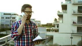 Biznesmen z smartphone i ogłoszenie towarzyskie organizatora pozycją na balkonie zbiory wideo