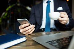 Biznesmen z smartphone pracuje w kawiarni Obrazy Stock