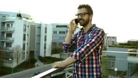 Biznesmen z smartphone robi rozmowie telefonicza, stoi na balco zbiory wideo