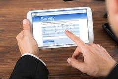 Biznesmen z telefonu komórkowego seansu ankiety formą obrazy stock