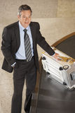 Biznesmen Z walizką Przy bagażu Carousel W lotnisku Fotografia Royalty Free