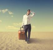 Biznesmen z walizki odprowadzeniem w pustyni zdjęcie royalty free