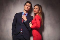 Biznesmen załatwia jego krawat podczas gdy kobiet leanins na on Obraz Stock