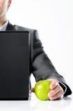 Biznesmen za laptopem z zielonym jabłkiem zdjęcie stock