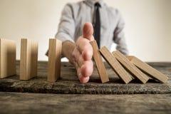 Biznesmen zatrzymuje domino skutek Fotografia Stock