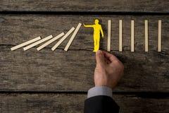 Biznesmen zatrzymuje domino skutek z papierowym wycinanki silhoue Obraz Stock