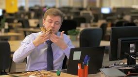 Biznesmena łasowania pizza przy jego biurkiem zbiory