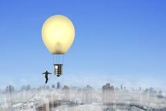 Biznesmena chodzący balansowanie na linie w kierunku lightbulb kształta gorącego powietrza bal Fotografia Stock