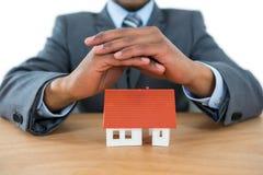 Biznesmena chronienia domu model z rękami Zdjęcie Stock