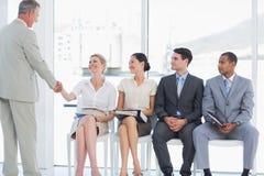 Biznesmena chwiania ręki z kobietą ludźmi czeka wywiad Zdjęcia Stock