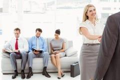 Biznesmena chwiania ręki z kobietą oprócz ludzi czeka wywiad Zdjęcia Stock