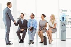 Biznesmena chwiania ręki z mężczyzna oprócz ludzi czeka wywiad Fotografia Royalty Free
