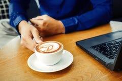 Biznesmena chwyta filiżanka kawy Filiżanka kawy jest na stole blisko laptopu Zdjęcia Royalty Free