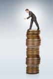 Biznesmena chylenie od moneta stosu obraz stock