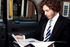 Biznesmena czytelniczy magazyn wśrodku taxi Obrazy Royalty Free