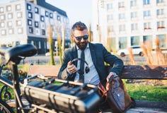 Biznesmena dojeżdżający z rowerowym obsiadaniem na ławce w mieście, mienie hełmofony fotografia royalty free