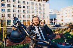 Biznesmena dojeżdżający z rowerowym obsiadaniem na ławce w mieście, słucha muzyka fotografia stock